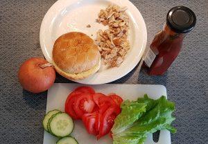 Bild på strimlad kyckling, grönsaker och hamburgerbröd innan montering