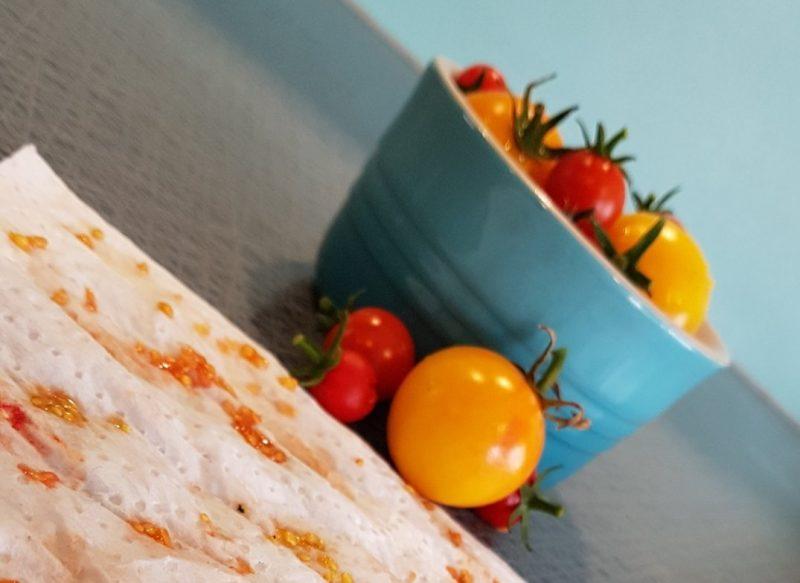 BIld på tomater i skål och ett hushållspapper med tomatkärnor.